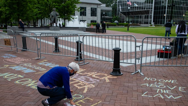 Brenda Reed, of Quincy, chalks just outside the barricades on the Hancock Adams Common on Friday, July 3.