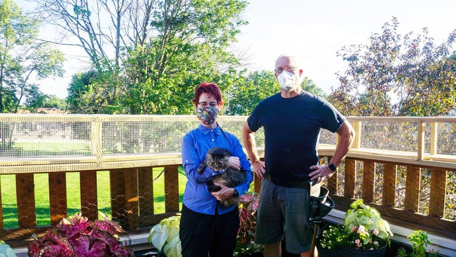 Nancy Loch and Douglas Rankin stand near potted plants on a garden balcony featuring a cat tunnel.