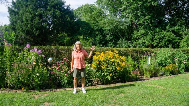 In her backyard garden, Ann Hyder stands in front of some of her cone flowers on Saturday evening.