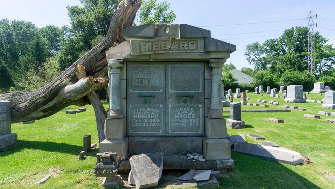 Parts of a mausoleum lay on the ground Monday morning at Hope Cemetery as a fallen tree rests heavily on the structure.