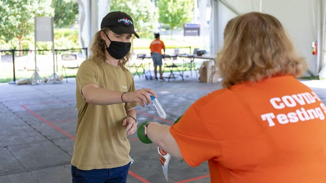 Graduate student Brett Cain completes COVID-19 saliva testing on Tuesday, July 7, 2020, in a tent on the University of Illinois at Urbana-Champaign campus.
