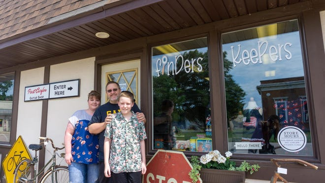 Owners of Finders Keepers, Aaron and Dara Duke stand with their son Ayden in front of the storefront.