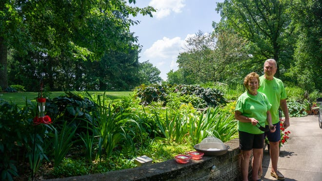 Janet, left, and Jan Cummings stand next to their garden on Saturday afternoon at their home near Lake Bracken.