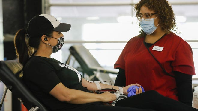 Cari Paller, left, of Chicago donates blood during a drive held at Guaranteed Rate Field in Chicago on May 8.