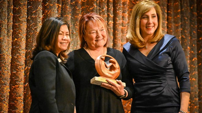 Ann Rundall, co-founder of Eliminating Racism 815, accepts the Racial Justice Award on March 2 from Paulina Sihakom, left, Rockford market executive for PNC Bank, and Kris Machajewski, CEO of YWCA Northwestern Illinois, at the YWCA Leader Luncheon at Giovanni's Conference Center.