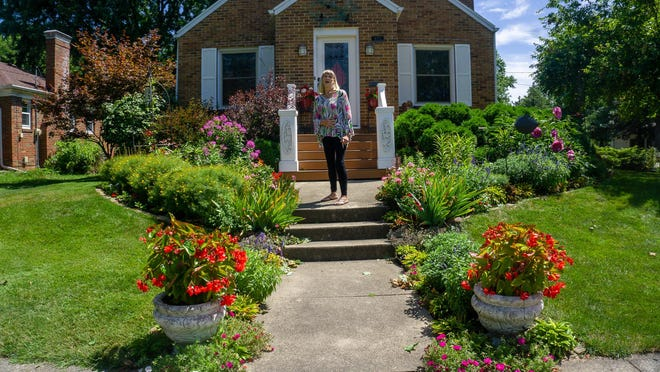 Carolyn Seeger stands in her front yard garden.
