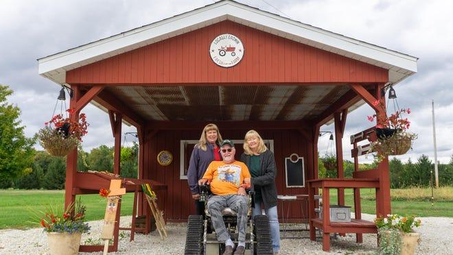 Barefoot Pickers part owners Sherilee Shepard, Bryan Eklund and Stefanie Eklund gather under their produce stand on Tuesday afternoon.