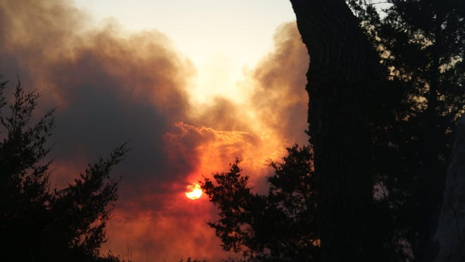The sun sets on the Wheat State Fire, a grass fire that scorched thousands of acres of farmland in western Harvey County this weekend.