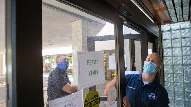 Topeka Fire Department inspector Chad Holthaus, right, tests the automatic doors to the city's Cyrus K. Holliday building Wednesday afternoon with Alan Stahl, left, public education officer.