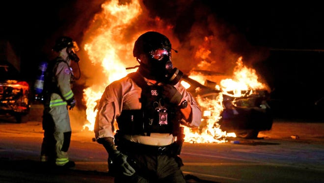 A police officer stands guard as firefighters try to put out the fire in a burning car in downtown in Miami Florida on Saturday, May 30, 2020 as protests in the wake of the police killing of George Floyd turn violent.