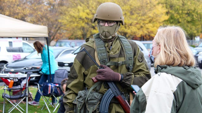 """An armed demonstrator speaks to a reporter during a """"freedom rally"""" in Allendale on Saturday, Oct. 24. A ban on open carry of weapons at Michigan polling places, put in place by Secretary of State Jocelyn Benson amid fears of attempts at voter intimidation on Election Day, was struck down in court earlier this week."""