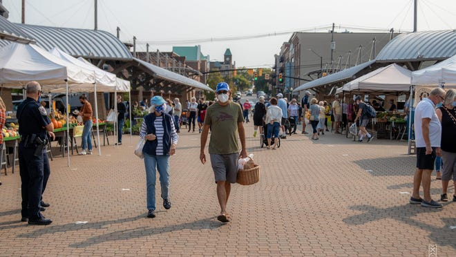 Holland Farmers Market shoppers wear face masks as they pick locally grown produce and baked goods.