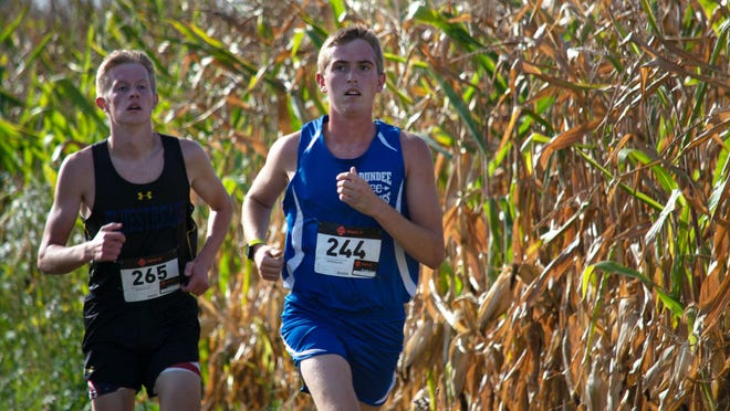 Dundee's Cole Cousino (right) leads Griffin Harmer of Ida in a cross country race Saturday. Cousino took first place, but Ida won the meet.