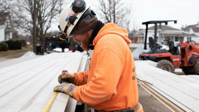 A steel worker continues work on a major project for Lakewood Construction despite cloudy weather. The company is celebrating 50 years in 2021.