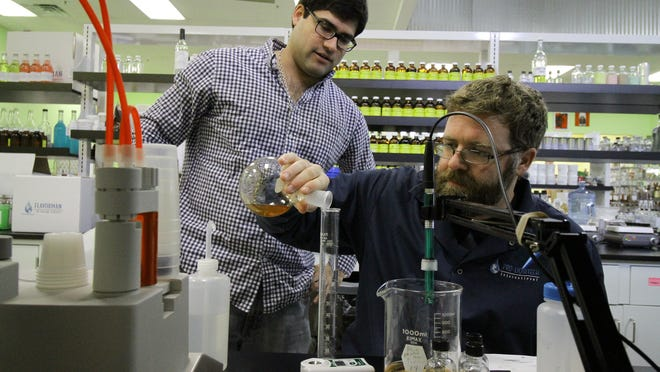 Production coordinator Evan Floyd, right, and distillery assistant Tyler Gomez add a measured ingredient into a client's alcoholic beverage at Flavorman's lab.