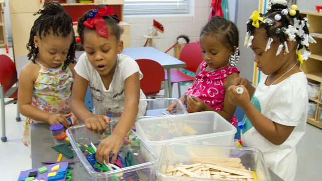 """Fro Hannah Alexander, from left, Amyri Robinson, Amari Prince, and Jaleah Braggs make crafts at the Art Center table in their """"Head Start"""" classroom in September at Unseld Early Childhood Education Center."""