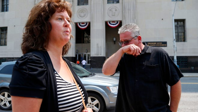 Terry Spurlock, right, of Holly, Mich., a former patient of Dr. Farid Fata, speaks with his wife Nikii outside federal court, Monday, July 6, 2015, in Detroit.