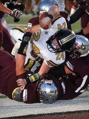 Henrietta quarterback Zack West (24) scores the Bearcats'