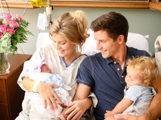 Erin Bates Paine and her husband Chad smile at their daughter Brooklyn Elise with their son Carson.