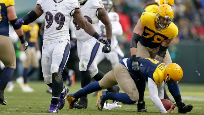 Baltimore Ravens outside linebacker Matt Judon (99) celebrates a safe as Green Bay Packers quarterback Brett Hundley (7) us helped up by Green Bay Packers offensive tackle Jason Spriggs (78) during the 4th quarter of the Green Bay Packers 23-0 loss to the Baltimore Ravens at Lambeau Field in Green Bay, Wis. on Sunday, November 19, 2017.