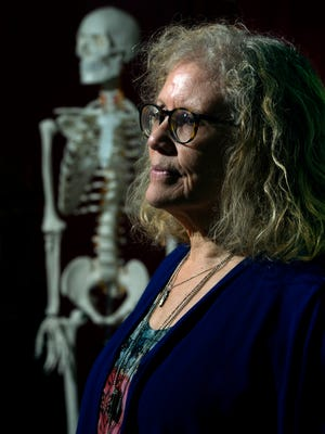 """Marty McCambridge, 64, who has lived her life with brittle bone disease, poses for her portrait at her home in Thousand Oaks. Behind her is the skeleton she uses in her one-woman show, """"The Nordic Princess Breaks the Ice,"""" which will be performed Friday and Saturday at California Lutheran University."""