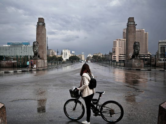 A 27-year old Egyptian artist stops with her bicycle