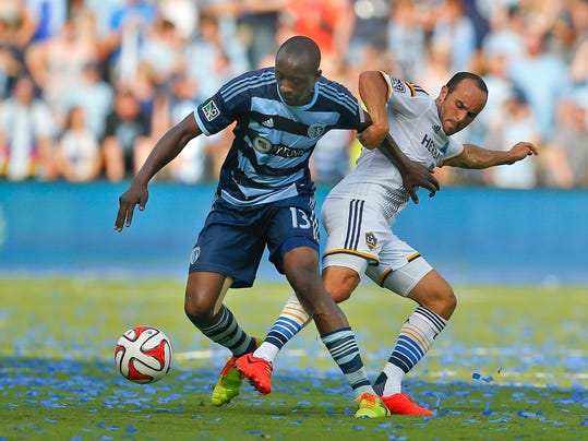 Los Angeles Galaxy's Landon Donovan, right, battles for the ball against Sporting Kansas City's Lawrence Olum during the first half of an MLS soccer game Saturday, July 19, 2014, in Kansas City, Kan. (AP Photo/Topeka Capital-Journal, CHris Neal)