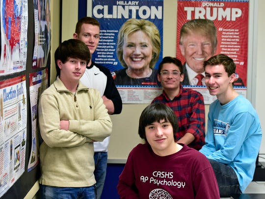 Students at Chambersburg Area Senior High School, Chambersburg, Pa., gather around posters of Hillary Clinton and  Donald Trump before watching the Presidential Inauguration in government class on Friday, January 20, 2017. From left, Seth Ardinger, Garrett Showalter, Kyle Chastulik, Izrael Wright and Quinn Mangan.