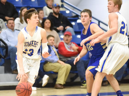 Mountain Home's Colton Peters dribbles around the screen of teammate Garrett Dietsche during the Bombers' 83-53 loss to Harrison.