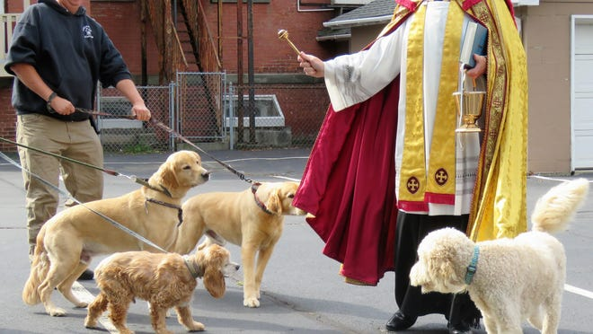 The Rev. Matthew C. Newcomb of St. Mary's Church in Port Jervis, with his own dog, Pius, at his side, blesses pets in the church parking lot Oct. 4.