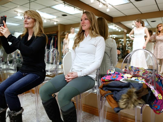 Kasey Bink's mother, Mary, and sister, Kristina, look at one of  the multiple dresses Kasey tried on at Tie the Knot Bridal Boutique in Green Bay.