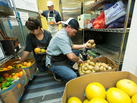 El Caldito Soup Kitchen volunteers Norma Rodriguez, left, Richard Hiss, center, and Damien Jones organize produce and other food items on Wednesday in the back pantry of the soup kitchen. Food donations are constantly sorted and rotated as they are delivered to the location.
