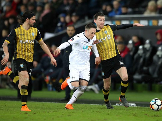 Sheffield Wednesday's George Boyd, left, watches as  Swansea City's Connor Roberts, centre and teammate David Jones battle for the ball, during the FA Cup, fifth round replay match between Swansea City and Sheffield Wednesday, at the Liberty Stadium, Swansea, Wales, Tuesday Feb. 27, 2018. (Nick Potts/PA via AP)
