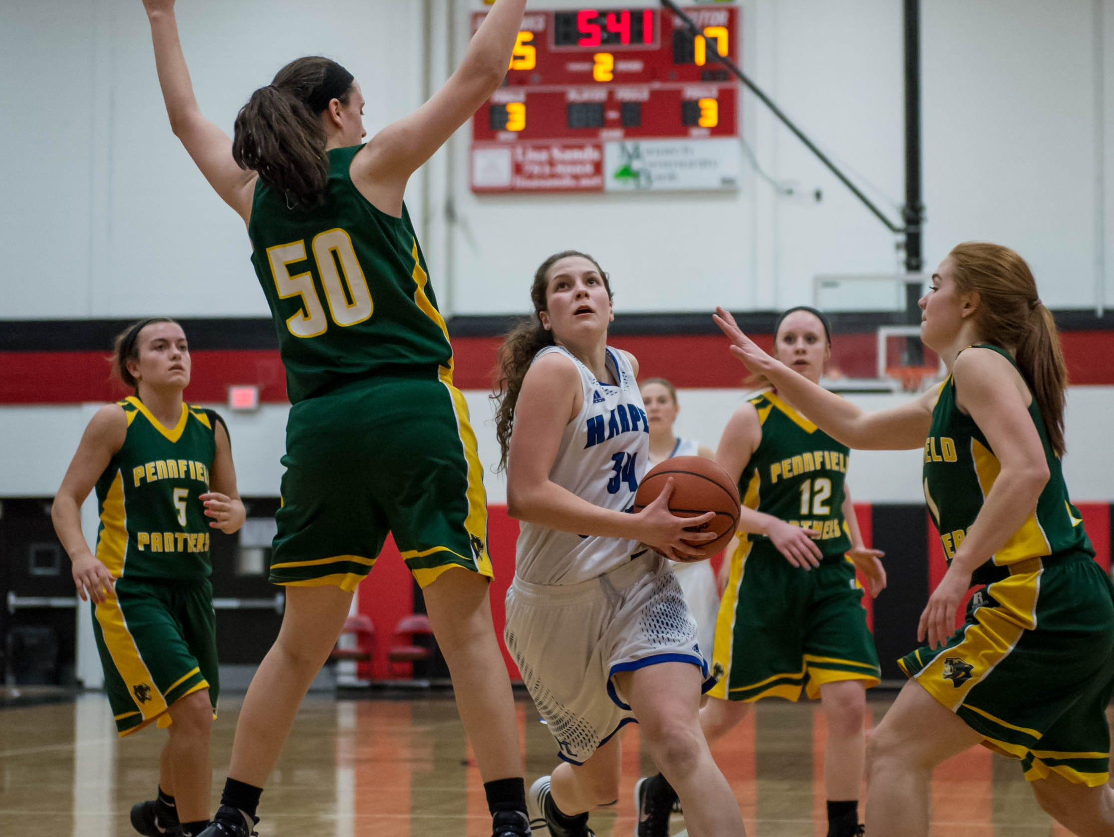Harper Creek's Faith Hayes (34) goes for the layup in first round of districts game at Marshall Monday evening.