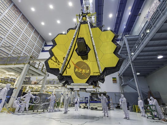 Technicians lift the mirror of the James Webb Space