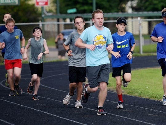 Assistant coach Eric Wilkes, right, runs with students