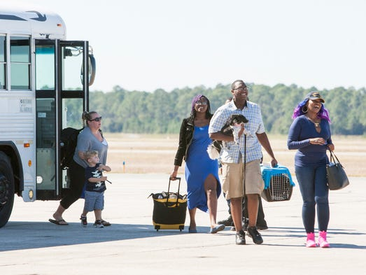 Military families board a plane at the Pensacola Naval