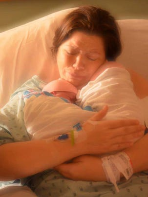 Shelly holds her newborn twin daughters, Isabel and