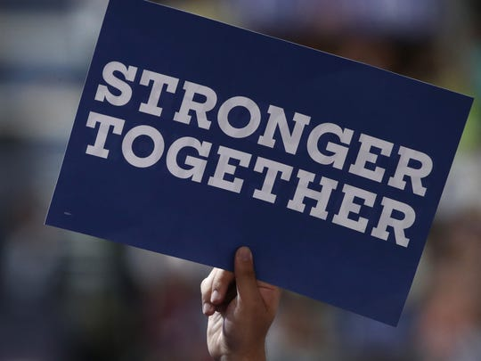 """A delegate holds a sign that reads """"Stronger together"""""""