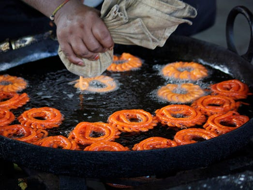 """Jalebi, common in South Asia, India and the Middle East, are delicate """"loops"""" of dough resembling thin funnel cakes. The batter for these sticky sweets is fermented, and after frying, the jalebi are soaked in syrup. Like most pastries, these treats are best eaten hot."""