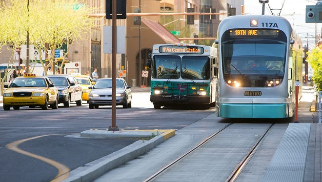 A Valley Metro bus and light rail train at Van Buren Street and Central Avenue in Phoenix on March 10, 2015.
