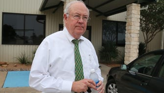 Ken Starr leaves a terminal at  Waco airport during his time as Baylor president.