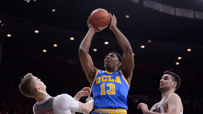 Feb 25, 2017: UCLA Bruins forward Ike Anigbogu (13) shoots the ball as Arizona Wildcats forward Lauri Markkanen (10) and center Dusan Ristic (14) defend during the first half at McKale Center.
