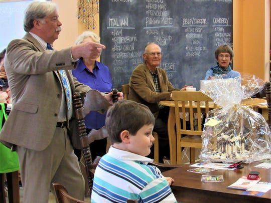 Sold! Among the many duties he has performed, Buddy Burkhardt acted as the auctioneer at last month's pie and cake sale fundraiser for the club.