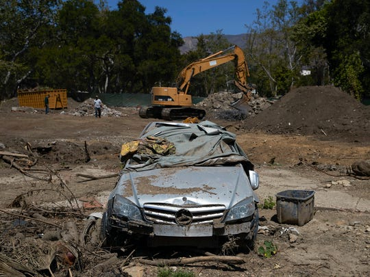 In this Wednesday, April 11, 2018, photo, a mangled car sits in a neighborhood devastated by a mudslide, in Montecito, Calif. Months after the mudslides nearly wiped the small community of Montecito off the map and killed multiple people, those who survived are still looking for and finding their belongings in the deep and hardened sludge.