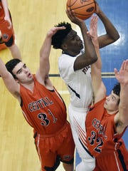 William Penn's Kristopher Johnson, center, shoots as he's defended by Central York's Niko Sobestanovich and Evan Czulada during a game in January. Johnson and the Bearcats open the District 3 Class AAAA tournament Wednesday against Carlisle, while Central York hosts Shippensburg.