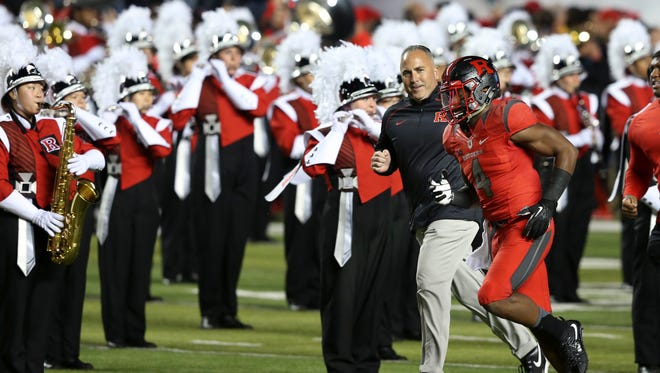 Rutgers head coach Kyle Flood, center left, runs past the marching band onto the field with wide receiver Leonte Carroo (4)   against Ohio State on Oct. 24.