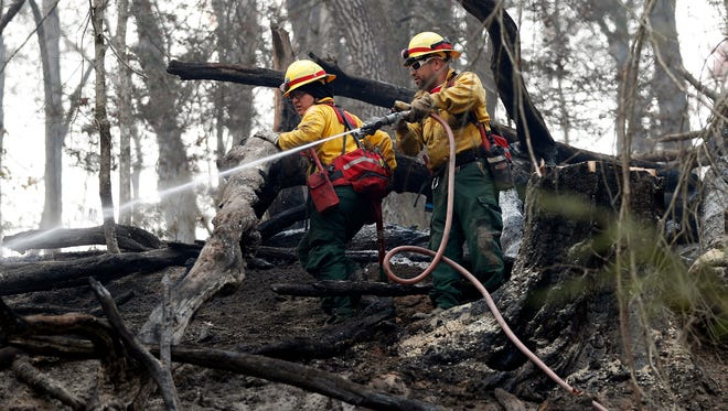 Firefighters Valarie Lopez, left, and Mark Tabaez work to cool hot spots after a wildfire burned a hillside Tuesday, Nov. 15, 2016, in Clayton, Ga. On Tuesday, the Tennessee Valley Authority issued a burn ban on its public lands across Tennessee and in parts of Alabama, Georgia, Kentucky, Mississippi, North Carolina and Virginia.