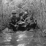 U.S. soldiers carry a wounded comrade through a swampy area during action in Vietnam in 1969. The Defense Department has agreed to reconsider the bad-paper discharges for thousands of Vietnam-era veterans who may have suffered from combat-related post-traumatic stress disorder but were kicked out of the military in the era before that became a diagnosable condition.