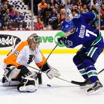 Canucks forward David Booth (right) moves the puck in front of Flyers goalie Steve Mason during the first period Monday night.